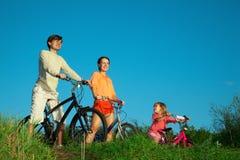 Pais com a filha em bicicletas na noite Foto de Stock Royalty Free
