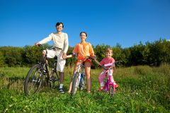 Pais com a filha em bicicletas no parque, dia Imagem de Stock