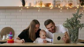 Pais com o bebê que joga com tabuleta digital video estoque