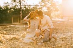 pais com o filho pequeno na roupa de linho próximo beijando ao descansar no feno imagens de stock royalty free