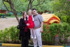 Pais com sua filha no campo de jogos no jardim fotos de stock