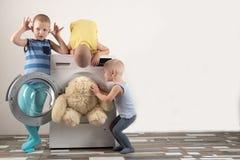 Pais comprados uma máquina de lavar nova As crianças tentam girá-lo sobre e lavar os brinquedos macios Os meninos felizes estão j foto de stock royalty free