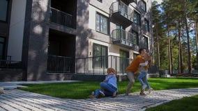 Pais da cena da família que jogam com as crianças exteriores filme