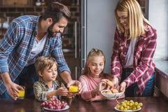 pais de sorriso e irmãos pequenos que comem o café da manhã imagens de stock