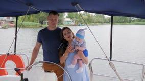 Pais e bebê alegres no fim de semana no mar, na mamãe, no paizinho e na jovem criança do fundo durante férias de verão no rio video estoque