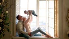 Pais e criança do menino que senta-se na janela video estoque