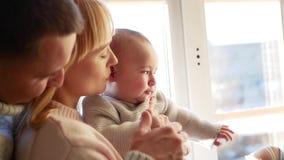 Pais e criança do menino que senta-se na janela vídeos de arquivo