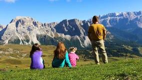 Pais e crianças em uma grama e vista das montanhas vídeos de arquivo