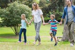 Pais e crianças que andam no parque Fotografia de Stock