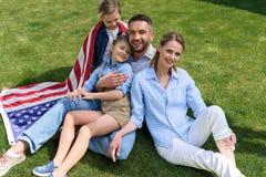 Pais e crianças que relaxam na grama com a bandeira americana, comemorando o 4 de julho - Dia da Independência Fotos de Stock