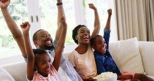 Pais e crianças que têm o divertimento ao olhar a televisão na sala de visitas filme