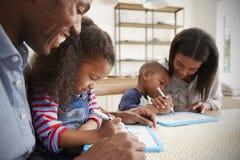 Pais e crianças que tiram em Whiteboards na tabela Imagens de Stock