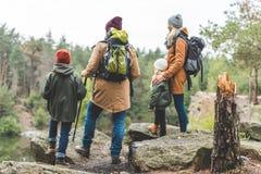 Pais e crianças que trekking na floresta fotos de stock