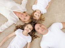 Pais e duas meninas que encontram-se no assoalho em casa Fotografia de Stock Royalty Free