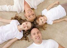 Pais e duas meninas que encontram-se no assoalho em casa Foto de Stock