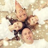 Pais e duas meninas que encontram-se no assoalho em casa Imagem de Stock