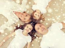 Pais e duas meninas que encontram-se no assoalho em casa Imagens de Stock