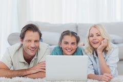 Pais e filha alegres que usa um portátil fotos de stock royalty free