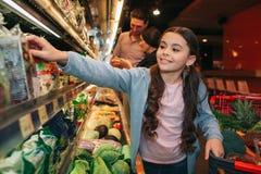 Pais e filha novos na mercearia A menina pegara a salada e o sorriso Alcança a mão à prateleira suporte dos pais fotografia de stock royalty free