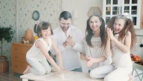 Pais e filhas sujados na farinha na cozinha, rindo, jogando, movimento lento
