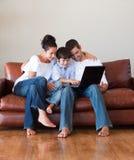 Pais e filho que jogam com um portátil fotografia de stock