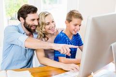 Pais e filho que usa o computador na sala de visitas imagens de stock royalty free