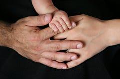 Pais e mãos da terra arrendada do bebê isoladas no preto Fotografia de Stock