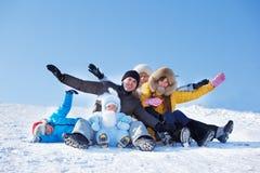 Pais e miúdos no monte nevado Fotografia de Stock