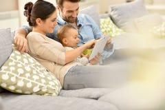 Pais e seu bebê que usa a tabuleta em casa Imagens de Stock Royalty Free