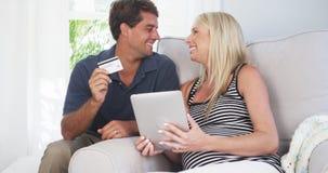 Pais entusiasmado que sorriem na câmera com cartão de crédito Imagens de Stock