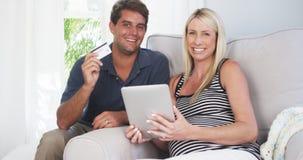 Pais entusiasmado que sorriem na câmera com cartão de crédito Fotografia de Stock Royalty Free