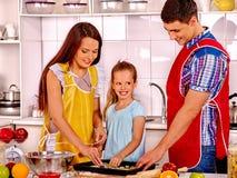 Pais felizes com as cookies do cozimento da filha Fotos de Stock Royalty Free