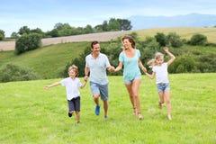 Pais felizes com as crianças que correm no campo Foto de Stock Royalty Free