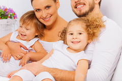 Pais felizes com as duas crianças adoráveis na cama Imagens de Stock Royalty Free