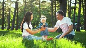 Pais felizes com filha da crian?a junto na grama verde no jardim filme