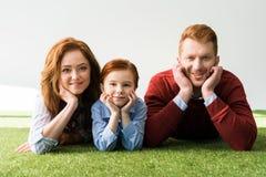pais felizes com a filha pequena bonito que encontra-se junto na grama e que sorri na câmera foto de stock royalty free