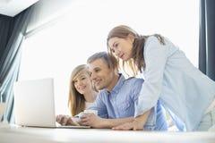 Pais felizes com a filha que usa o portátil em casa imagem de stock royalty free