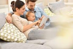 Pais felizes com seu bebê que usa a tabuleta Fotos de Stock