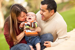 Pais felizes da raça misturada que jogam com seu filho imagens de stock