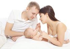 Pais felizes e bebê que encontram-se na cama Foto de Stock