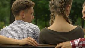 Pais felizes e crianças adolescentes que sentam-se no banco de parque, tendo o divertimento no fim de semana video estoque