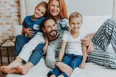 Pais felizes e duas crianças junto na cama fotos de stock royalty free