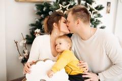 Pais felizes no assento de aperto e de beijo do amor no fundo perto da árvore de Natal imagem de stock