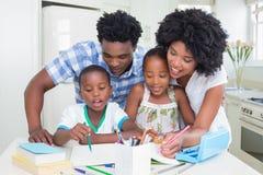 Pais felizes que ajudam crianças com trabalhos de casa fotografia de stock