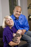 Pais felizes que embalam o bebê no regaço em casa Foto de Stock Royalty Free