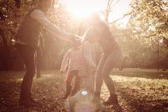 Pais felizes que jogam com a filha no parque imagens de stock royalty free