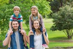 Pais felizes que levam crianças em ombros no parque fotografia de stock royalty free