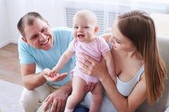 Pais felizes que passam o tempo com sua menina Fotografia de Stock Royalty Free