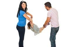 Pais felizes que têm o divertimento com sua filha Imagem de Stock Royalty Free