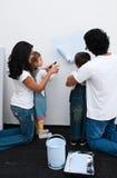 Pais Loving que ajudam suas crianças a pintar foto de stock